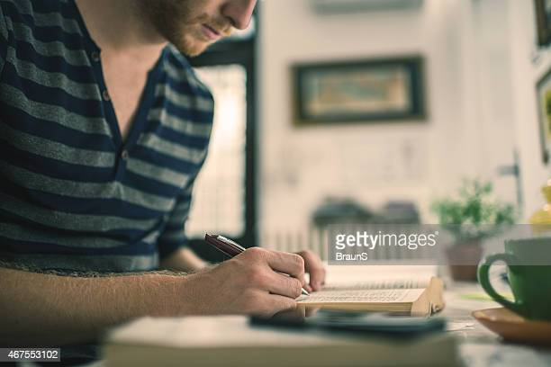 Unrecognizable male student writing and studying.