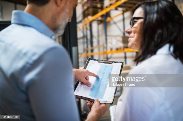 Unrecognizable man and woman manager or supervisor with clipboard in a warehouse.