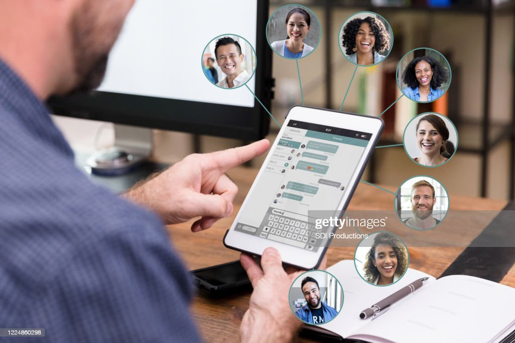 Unrecognizable man chats online with business associates : Stock Photo