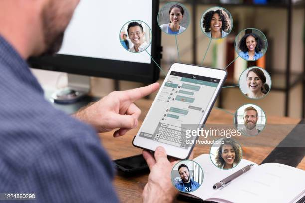 unrecognizable man chats online with business associates - employee engagement stock pictures, royalty-free photos & images