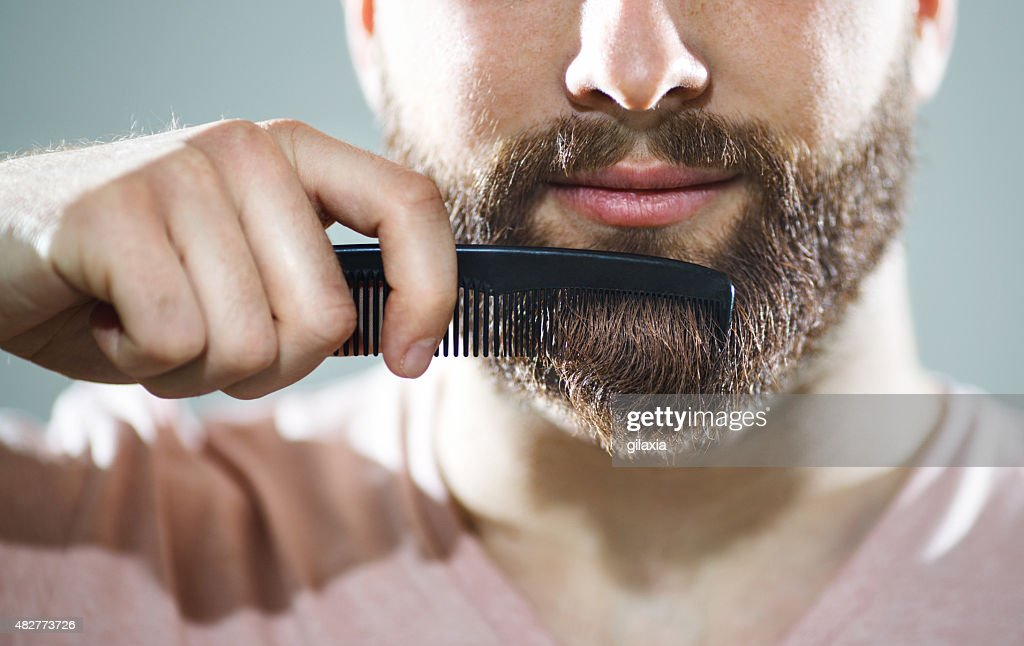 Unrecognizable man combing his beard : Stock Photo