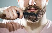Unrecognizable man combing his beard