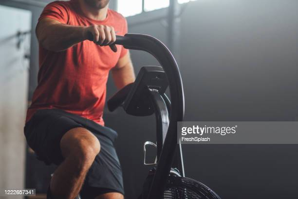 unrecognizable  man doing exercise on a gym stationary bike, gym concept - cardiovascular exercise stock pictures, royalty-free photos & images