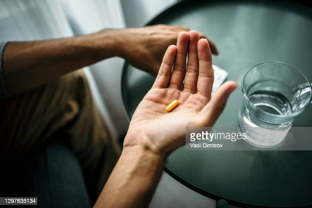 unrecognizable man holding a pill in front of a table with glass of water. medical treatment / drug use concept. - anti depressant stock pictures, royalty-free photos & images