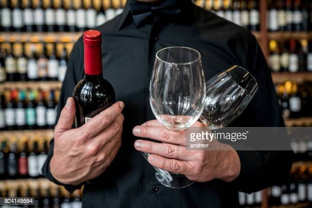 Unrecognizable man holding glasswines and a wine bottle at a restaurant