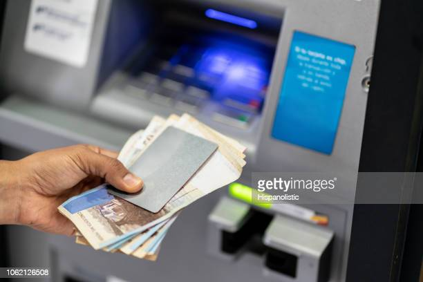 unrecognizable man holding his debit card and cash after withdrawing from atm - colombia stock pictures, royalty-free photos & images