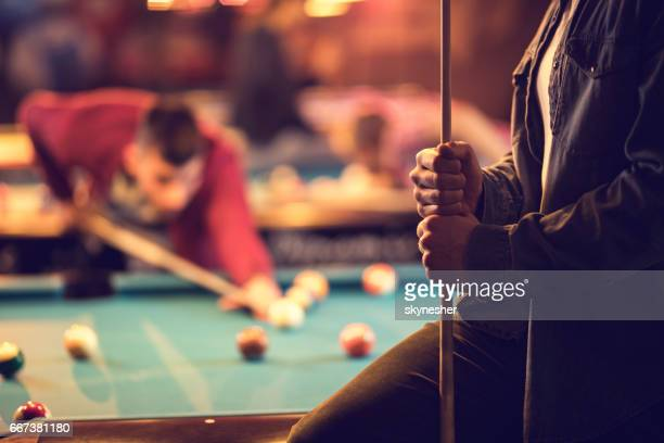 Unrecognizable man holding pool cue in a pool hall.