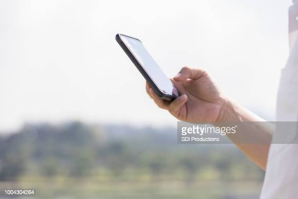 unrecognizable man holds smart phone outside - thumb stock pictures, royalty-free photos & images