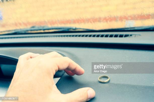unrecognizable man is going to take a gold wedding ring on the car dashboard. - caught cheating stock pictures, royalty-free photos & images