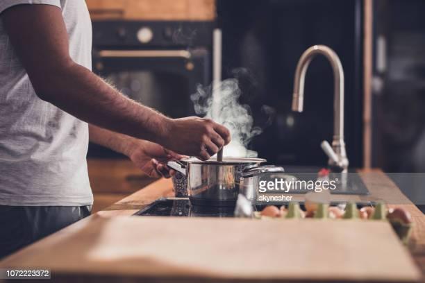 認識できない男はキッチンと攪拌しながらスープのランチを作るします。 - シチュー鍋 ストックフォトと画像