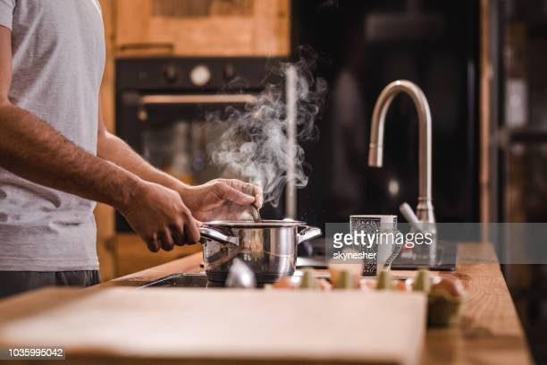 unrecognizable man stirring soup in a saucepan while making lunch in the kitchen. - saucepan stock pictures, royalty-free photos & images