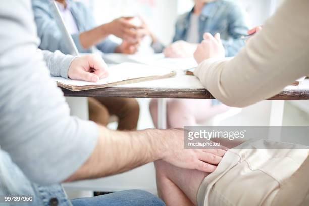 onherkenbaar man streelde dame benen en probeert te krijgen in haar broek terwijl ze zitten aan tafel tijdens vergadering - ongewenste intimiteit stockfoto's en -beelden