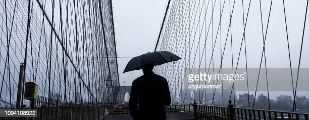 unrecognizable man walking at brooklyn bridge - film noir style stock pictures, royalty-free photos & images
