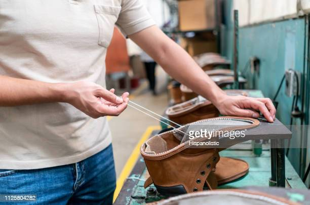 Unrecognizable man working at a shoe factory sewing boots