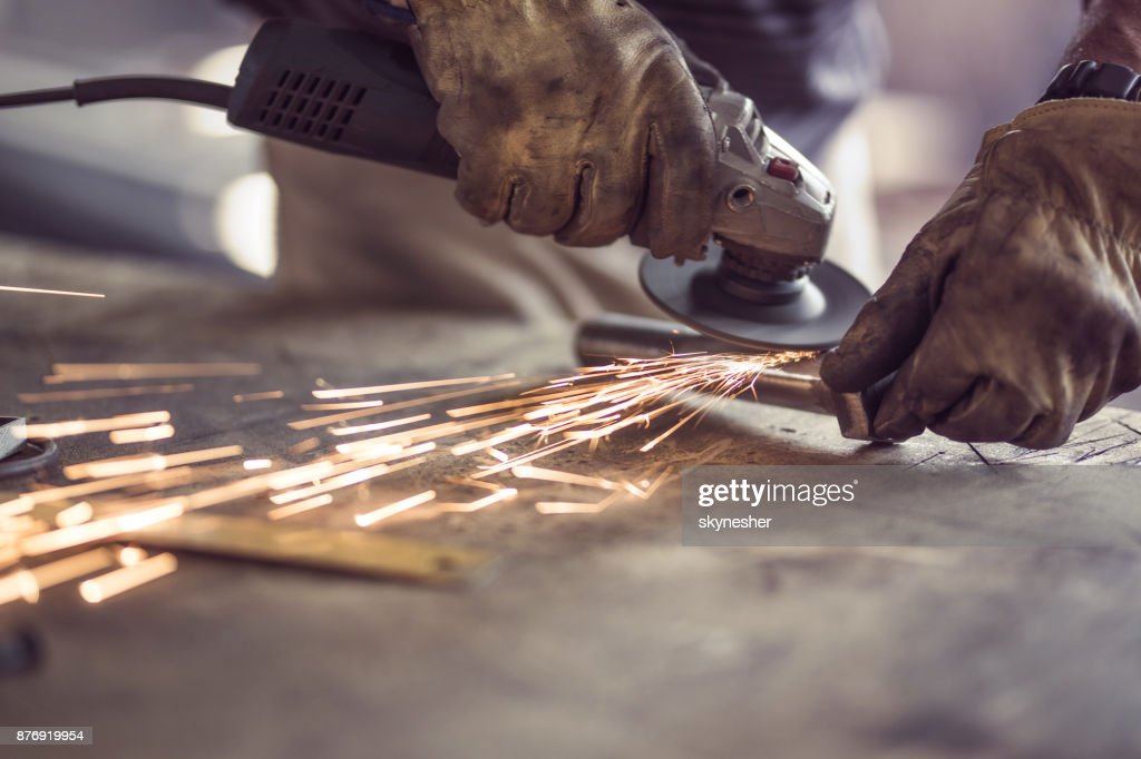 Unrecognizable manual worker cutting iron with a saw in a workshop. : Stock Photo