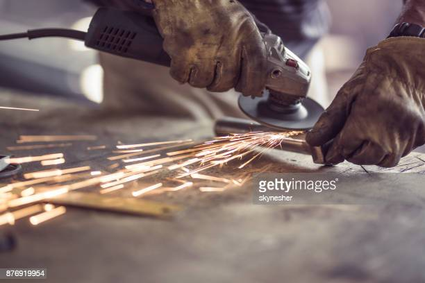 unrecognizable manual worker cutting iron with a saw in a workshop. - welding stock photos and pictures