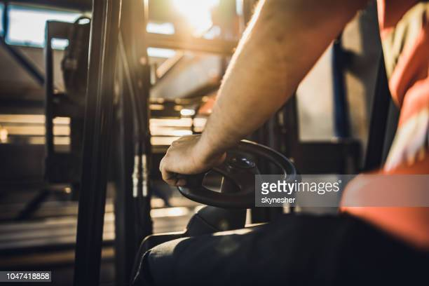 unrecognizable manual worker driving a forklift. - forklift stock pictures, royalty-free photos & images