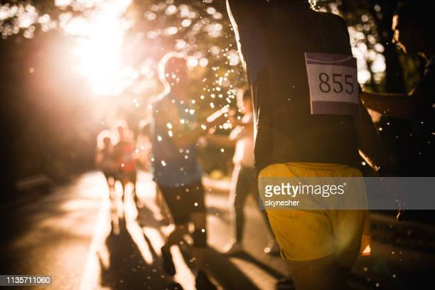 unrecognizable marathon runner taking refreshment during a race in nature. - half_marathon stock pictures, royalty-free photos & images