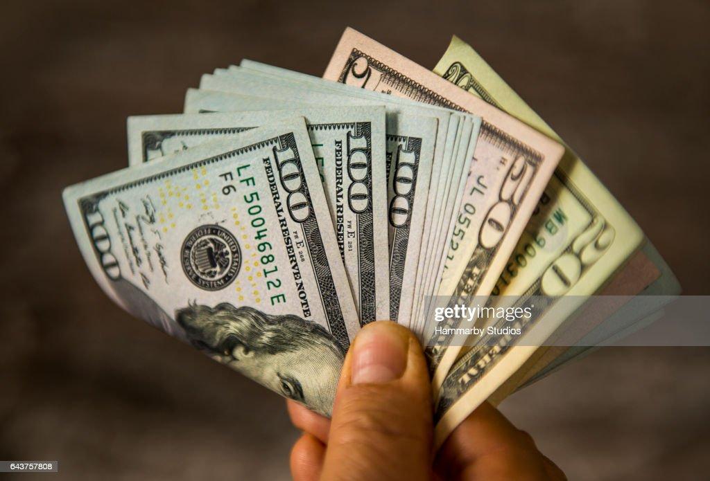 Nicht erkennbare reifer Mann hält US-Dollarnoten : Stock-Foto