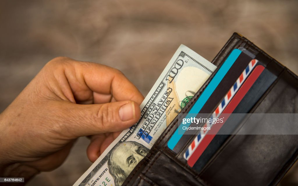 Unrecognizable mature man putting USA Dollar bill into wallet : Stock Photo