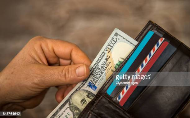Unrecognizable mature man putting USA Dollar bill into wallet