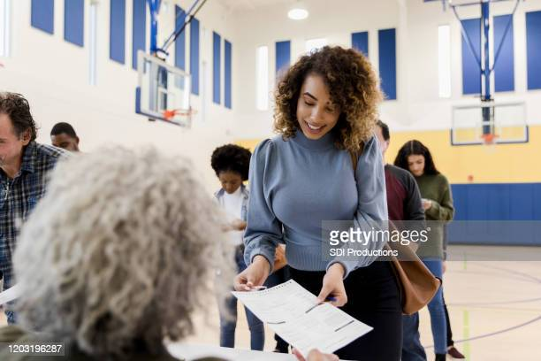 unrecognizable mature woman assists mid adult woman with voting document - voting stock pictures, royalty-free photos & images