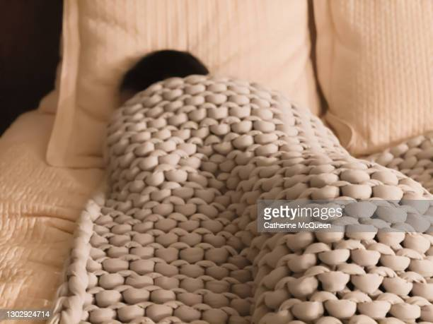 unrecognizable mixed-race female soundly sleeping under weighted blanket - blanket stock pictures, royalty-free photos & images