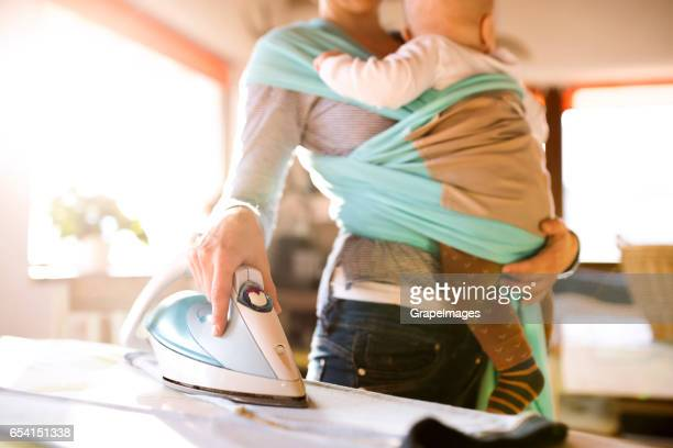 Unrecognizable mother at home ironing clothes with baby in sling