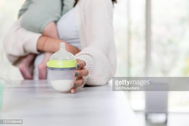 認識できない母親が哺乳瓶を拾う - 哺乳瓶 ストックフォトと画像
