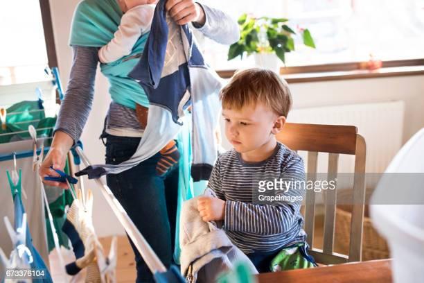 Onherkenbaar moeder met baby in draagdoek, zoon om haar te helpen met Wasserij