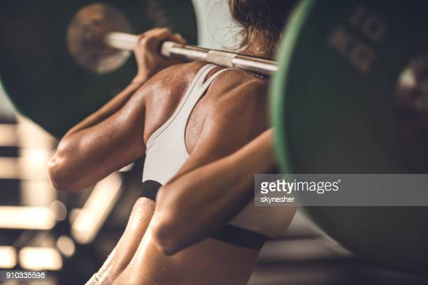 unrecognizable muscular build woman doing strength exercises with barbell in a gym. - weight training stock pictures, royalty-free photos & images