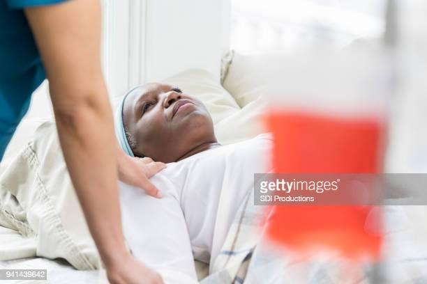 unrecognizable nurse comforts senior patient - cancer illness stock pictures, royalty-free photos & images
