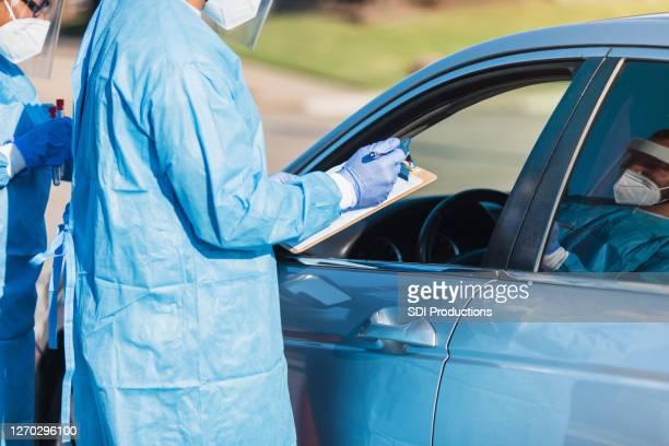 認識できない看護師がcovid検査場で患者から情報を収集 - ドライブスルー検査 ストックフォトと画像