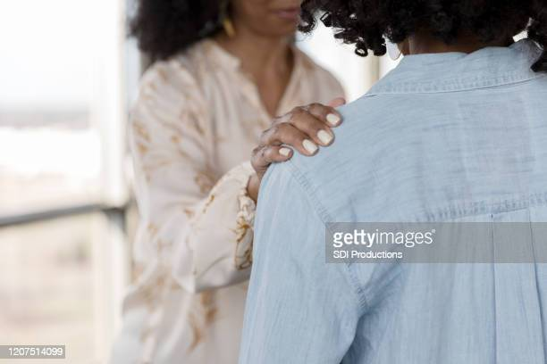 unrecognizable older woman comforts younger woman - hand on shoulder stock pictures, royalty-free photos & images