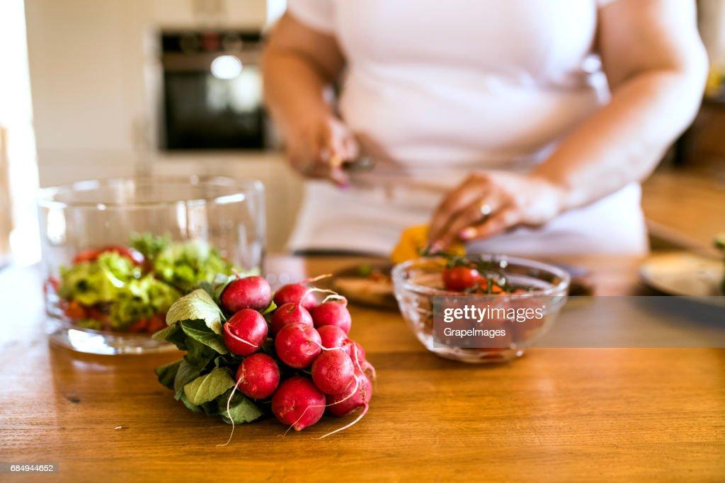 認識できない肥満女性家では、彼女のキッチンでおいしいヘルシーな野菜サラダを準備しています。 : ストックフォト