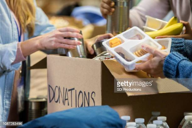 unrecognizable people donate food to food bank - food bank stock pictures, royalty-free photos & images