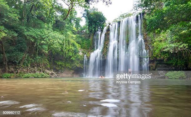 Unrecognizable people enjoying waterfall at Costa Rica jungle