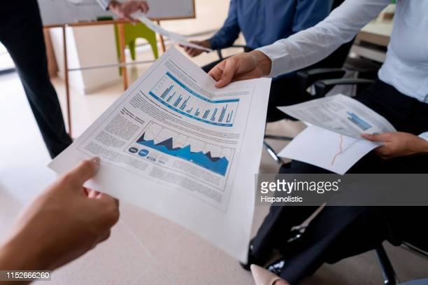 unrecognizable people in a meeting handing documents - hispanolistic stock photos and pictures