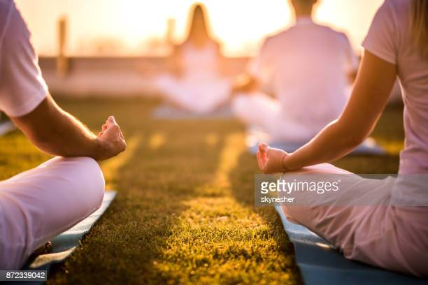 Unrecognizable people practicing Yoga on exercise mats at sunset.