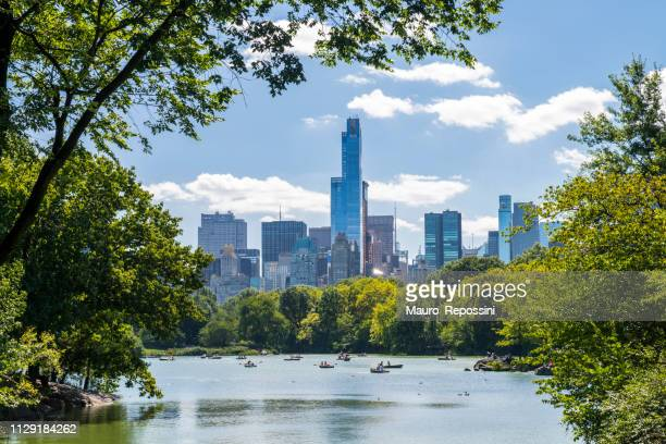 unrecognizable people rowing in a lake during summer at central park, midtown manhattan, new york city, usa. - central park stock pictures, royalty-free photos & images
