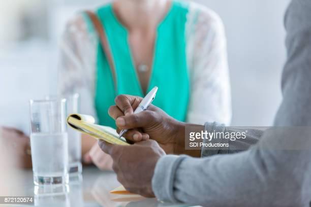 Irreconocibles personas sentarse en una mesa y una lluvia de ideas