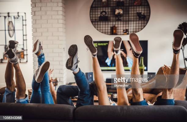 unrecognizable people's legs on sofa at home. - roommate stock pictures, royalty-free photos & images