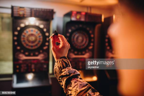 Unrecognizable person aiming at dartboard in a pub.