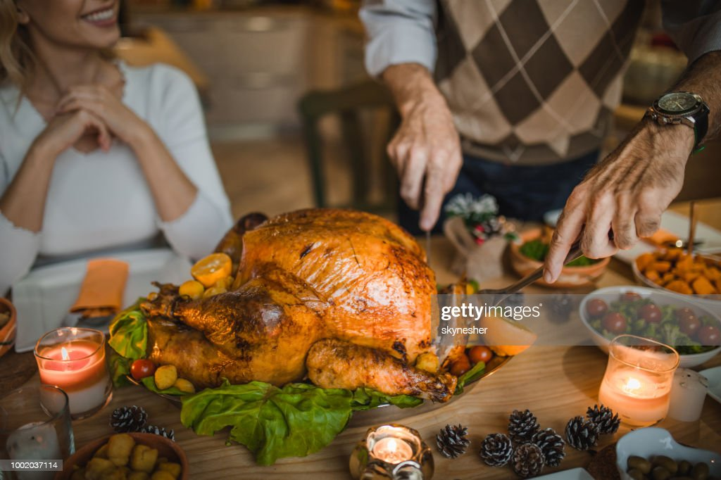 Unrecognizable person carving roasted turkey during Thanksgiving dinner at dining table. : Stock Photo