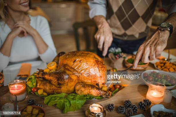 unrecognizable person carving roasted turkey during thanksgiving dinner at dining table. - turkey meat stock pictures, royalty-free photos & images