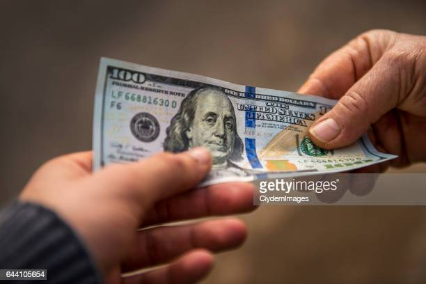 Unrecognizable person giving other person USA Dollar bill