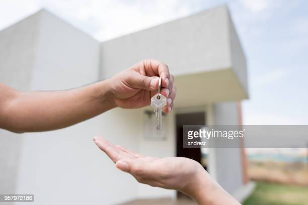unrecognizable person giving the keys of a house to a new home owner - passing giving stock photos and pictures