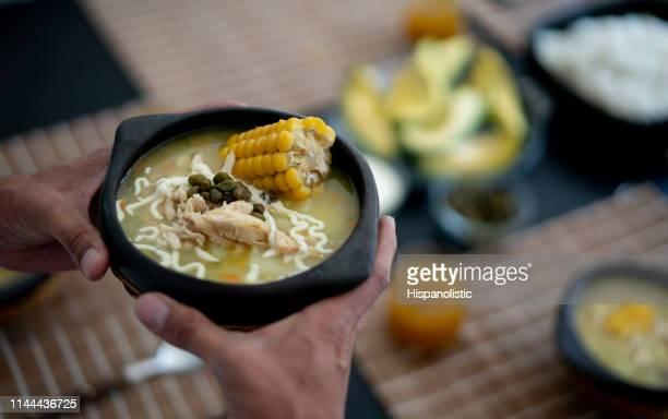 persona irreconocible sosteniendo un delicioso ajiaco listo para servir en la mesa - colombia fotografías e imágenes de stock