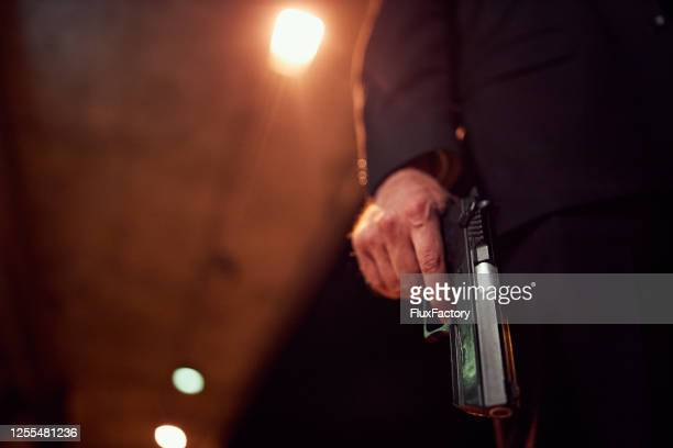 unrecognizable person holding a handgun at night - gun stock pictures, royalty-free photos & images