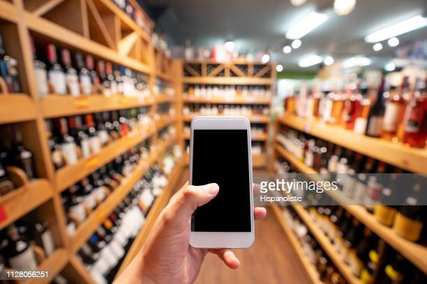 unrecognizable person holding a smartphone at a wine cellar - liquor store stock pictures, royalty-free photos & images